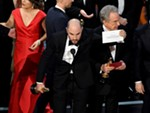 """La La Land"" producer Jordan Horowitz holds up the winner card reading actual Best Picture winner ""Moonlight"" with actor Warren Beatty onstage during the 89th Annual Academy Awards."