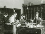 Women work side by side with men in early WSC chemistry lab.