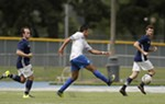 FCM Portland forward Luis Galeano, center, attempts a shot on goal while defended by Spokane Shadow defender David Starkovich (4) and defender Kyle Morris during the first half.