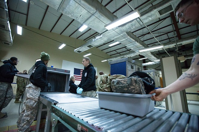 US Army 391st Military Police Battalion Detachment 5 Corporal Jesse Hutchin, right, moves a bucket of personal bags after screening at the customs office. - YOUNG KWAK