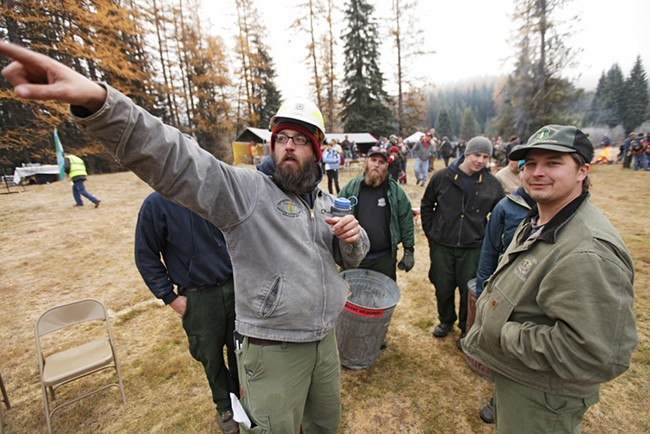 U.S. Forest Service employee Ben Curtis, center, reviews some procedures before the tree is cut. - YOUNG KWAK