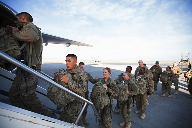 US military service members returning from combat deployment in Afghanistan board an Omni Air International 777 for a flight home. - YOUNG KWAK