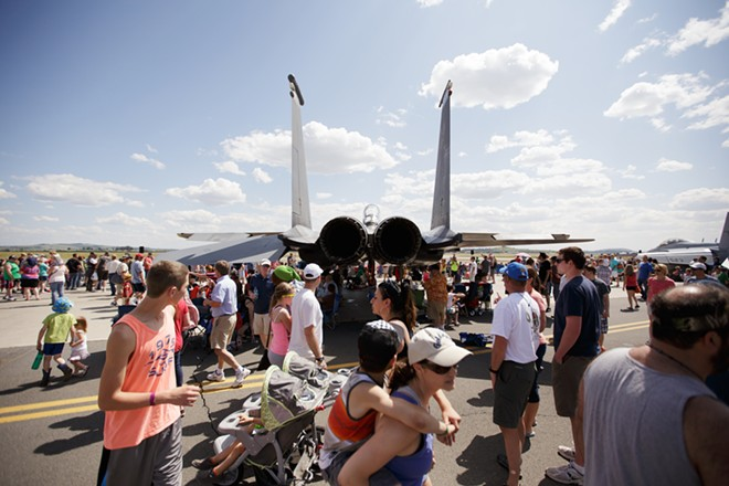 Visitors walk past an F-15E. - YOUNG KWAK