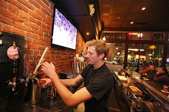 Bartender Levi Alford pours a beer at Post Street Ale House on Sunday. - YOUNG KWAK