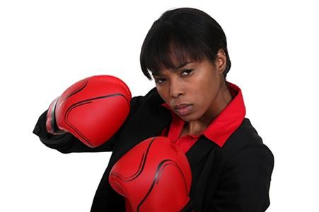 Female office worker wearing boxing gloves