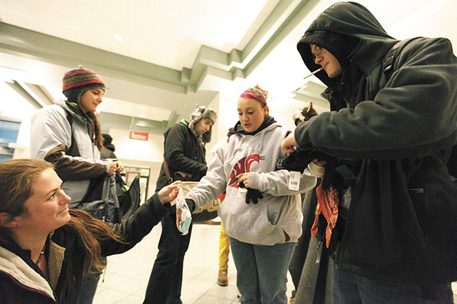 YouthREACH's Carletta Gaston, left, hands out gloves and toiletries at the STA Plaza. - YOUNG KWAK