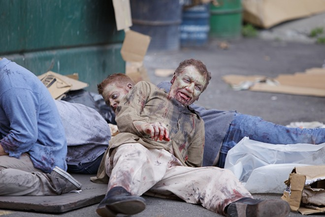 Zombie extras recover after acting a scene where they had to fall to a hail of gunfire. - YOUNG KWAK