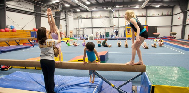 Balance beam coach Rebecca Belrose helps gymnasts with their moves