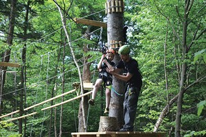Gabe Tharp helps son Wylie onto the zip line