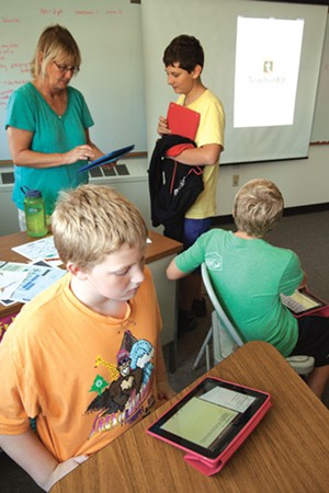 Hinesburg Community School health teacher Cindy Stanley helps students navigate lessons on the iPad.