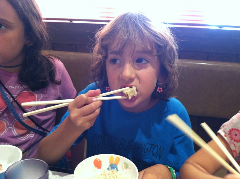 Lola masters eating with chopsticks.