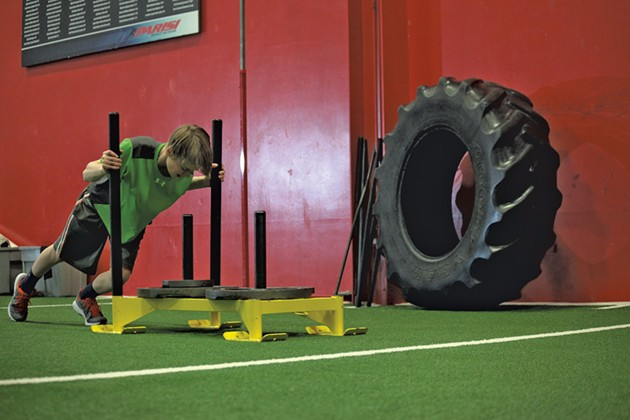 Matt Reinfurt, 13, pushes the Prowler Sled, a tool used in Parisi to develop speed and strength. - MATTHEW THORSEN