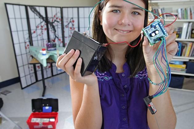 Amelia holding ChampBot parts - MATTHEW THORSEN