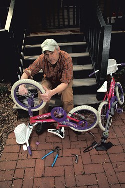 Erik Esckilsen fixes his twin daughters' bikes - MATTHEW THORSEN