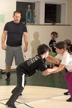 Coach Scott McPherson watches Ivy and Nicholas Forguites practice - MATTHEW THORSEN
