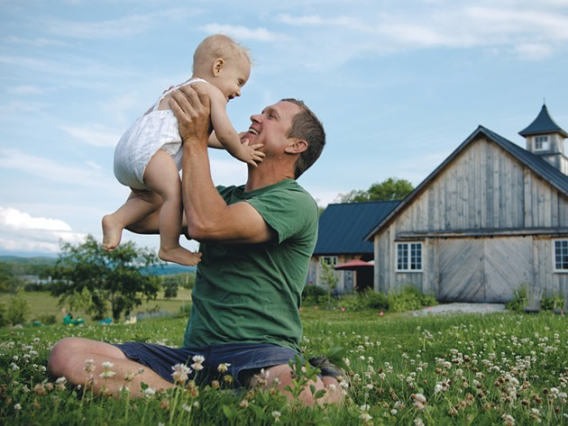 Adam Hausmann, 44, owner of Adam's Berry Farm in Charlotte, with son Wilder Rye, 9 months - SAM SIMON