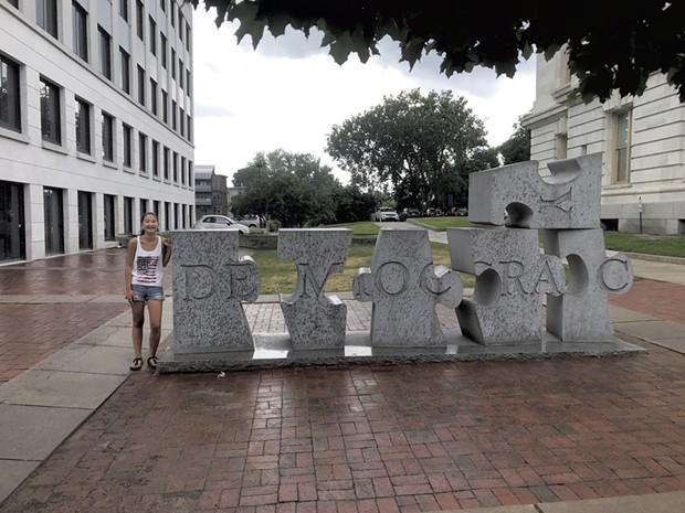 """Grace Heller next to W.F. Herrick's sculpture """"Democracy"""" in Burlington (Activity 50)"""