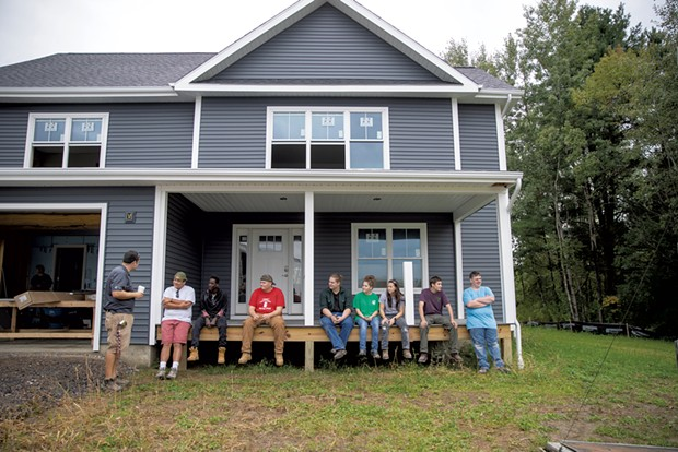 Essex tech instructor Chris Welch (left) reviews the morning's progress with students at the home they are building in Essex Junction - JAMES BUCK