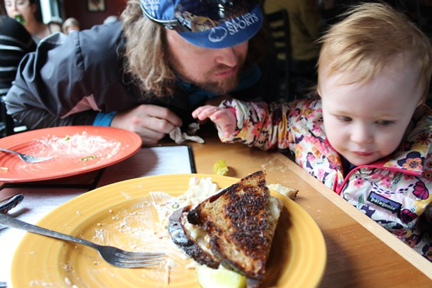 Elise helps eat a tempeh Reuben sandwich at Lost Nation Brewing - COURTESY SARAH GALBRAITH