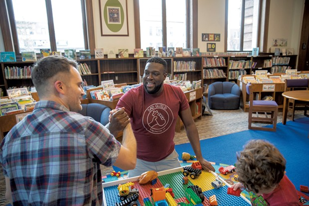 Dad Guild members Marlon Fisher (right) and Patrick Pierce greet each other at a library playgroup - JAMES BUCK