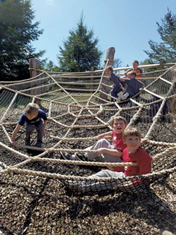 Children climbing on a spider web play structure in VINS' Adventure Playscape - COURTESY OF VINS