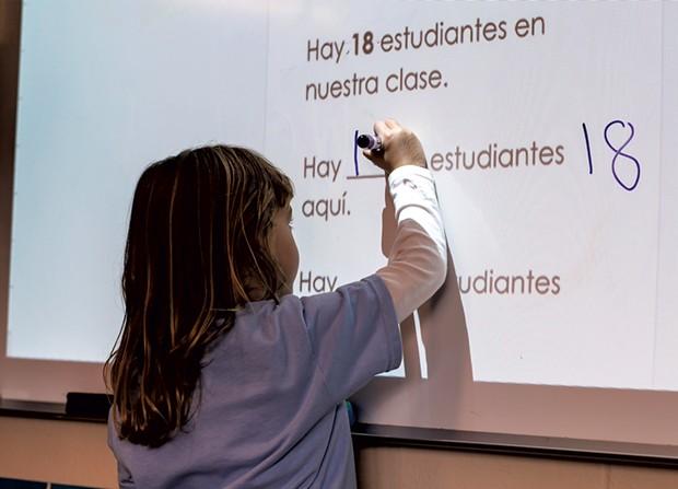 A Spanish immersion kindergartner fills in the blank on the whiteboard - GLENN RUSSELL