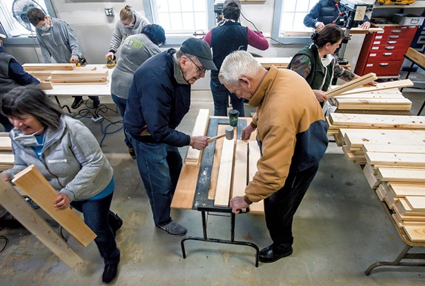 Volunteers use a mallet to make holes in wood that will eventually become a bed - GLENN RUSSELL