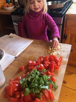 Rosie with ingredients for marinara sauce - HEATHER MOORE