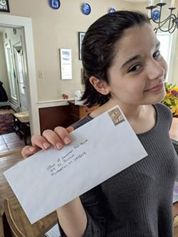 Evelyn Fleming holding up her letter to Gov. Phil Scott