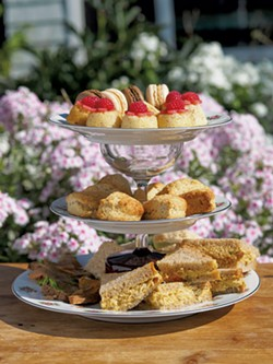 A tiered tray holding cookies, scones and finger sandwiches - ANDY BRUMBAUGH