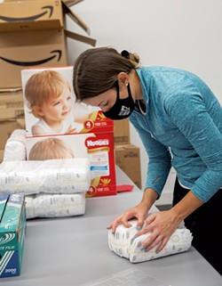 A volunteer bundling diapers in September - COURTESY OF AMANDA HERZBERGER