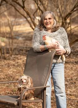 Tomasi holding a chicken alongside her dog Gigi - CAT CUTILLO