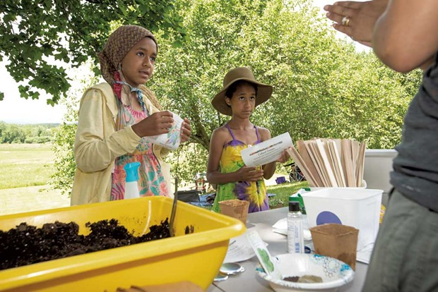 Ava Mirembé and Esmé Ssanyu Grundy Bruce listen to Hanron's instructions at the black eyed peas and collard greens planting station at the Juneteenth celebration - CAT CUTILLO