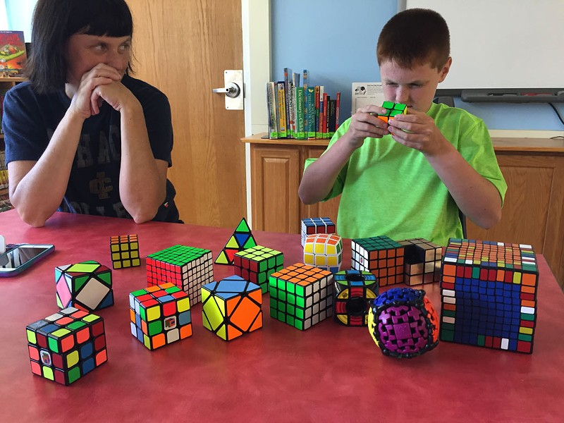 Brady solves a puzzle while his mom looks on