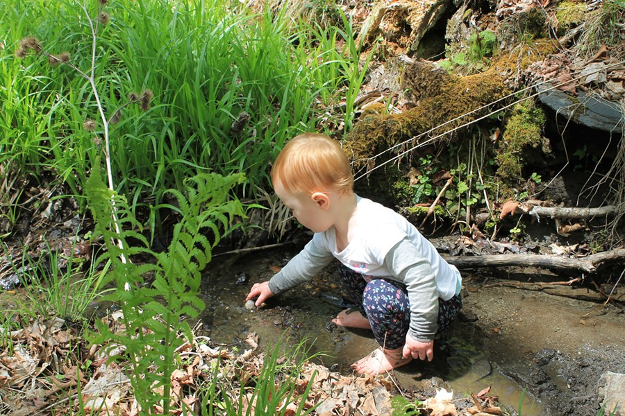 Elise takes a break from trail work to play in a stream - SARAH GALBRAITH