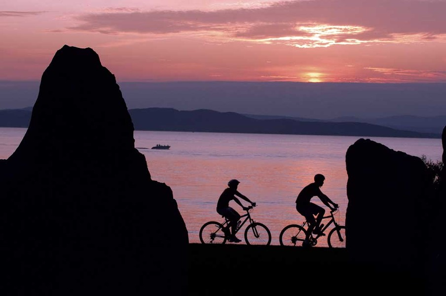 Cyclists on the Burlington Greenway at night
