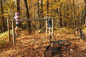 Dillon (left) and Harper play on parallel bars in the woods of Trapp Family Lodge