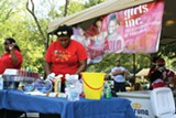 ALEXANDRA PUSATERI - A volunteer prepares the food at the Girls - University kickoff event at Marquette Park.