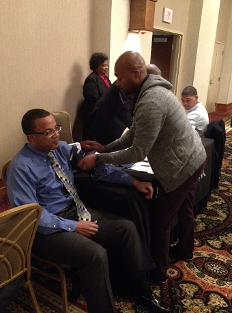 Adrian Newson gets his blood pressure checked during Wednesday's Healthy Shelby luncheon. - LOUIS GOGGANS