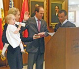 JB - As wife and daughter look on, Conra takes the oath from Judge Tarik Sugarmon.
