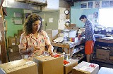 Barbara Bloomfield prepares boxes for the Farm's book publishing business. - JUSTIN FOX BURKS