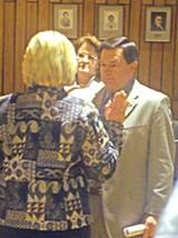 JB - County clerk Debbie Stamson adminisers the oath of office to Trustee Paul Mattila as Mattila's wife Margaret looks on.