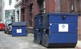 Dumpsters crowd a downtown alley.