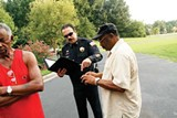 JUSTIN FOX BURKS - During a National Night Out event this month, resident Earvin Clay explains a break-in to the MPD's Major Oakley.
