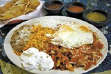 El Palmar's huevos con chilquilas, fried eggs with a side of rice and beans - JUSTIN FOX BURKS