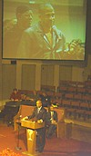 Former fellow townsman Eric Coleman, now of the <i>Flyer</i> staff, looms large on the jumbo screen at Mississippi Boulevard Christian Church as he greets Nagin Wednesday night.