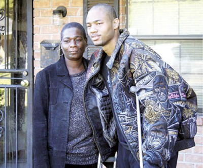 Former Tiger and Grizzlies player Antonio Burks (right), a recent gunshot victim, appeared with his mother, Connie, at her North Memphis rental home Monday to solicit county commission support for builder Harold Buehler's efforts to develop new lots. - RICK MAYNARD