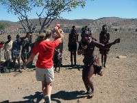 Jacy Gentry dances with a Himba woman while children look on. - PATRICK DEVEAU