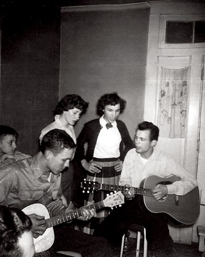 Jim Cannon (left) and Johnny Black (right) pick and sing at Cannon's mother's house at party for Cannon before he left for Korea. Carolyn Black (right), Vivian Miller (middle), and Joseph Buck Cannon (left) watch and sing along behind them. Johnny, who is left handed, would flip his guitar around and play it upside down. - COURTESY CANNON FAMILY