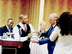 Party chair Bryan Carson gives Kyle an award. - JB
